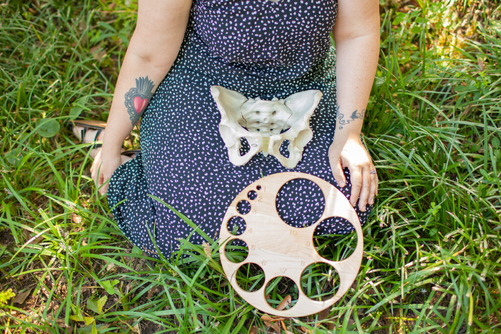 zoe etkin doula holding pelvis model and dilation model outside in grass
