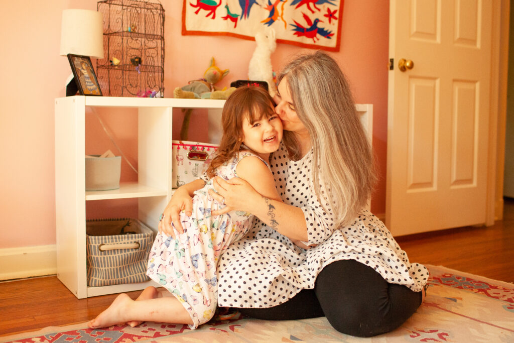 doula zoe etkin in child's bedroom with daughter who is smiling